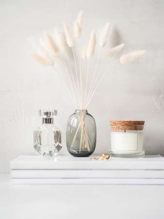 Modern feminine still life of white dry lagurus flower in glass vase, glass scented candle and a bottle of perfume on stack of white magazines on light background. Front view. Copy space
