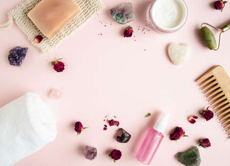 Frame from various cosmetics and minerals on pink background. Top view. Copy space