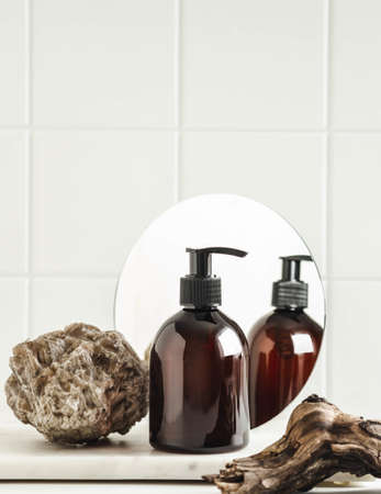Stone, piece of wood and brown cosmetic bottle in creative natural composition with mirror on white tile background. Copy space. Front view. Product mock up