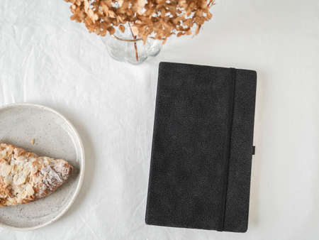 Black pocket journal, croissant and dry flowers in glass vase on white textured background. Top view. Study, education, work concept. Flat lay. copy space. Minimal modern composition. Stock fotó