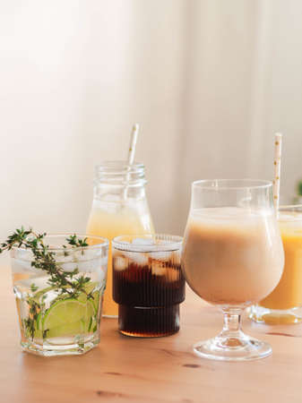 Various refreshing non-alcoholic drinks in glasses with ice. Fruit juice, lemonades, iced coffee, smoothies on wood table. Copy space. Front view