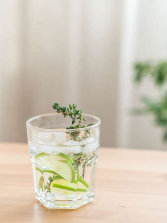 Summer homemade refreshing drink with lime, ice cubes and thyme on wooden background. Front view. Copy space Stock fotó