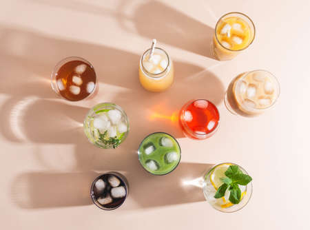 Various refreshing non-alcoholic drinks in glasses with ice. Different juice, homemade lemonade, iced coffee, iced fruit tea and smoothies on beige background. Copy space. top view