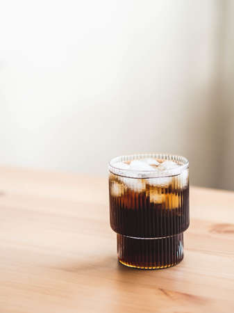 Cola glass with ice cubes on wood table in room. Front view. Copy space