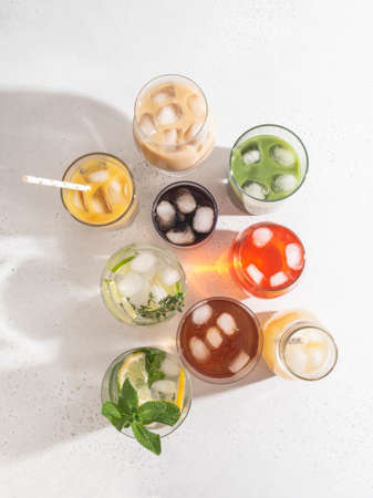 Various refreshing non-alcoholic drinks in glasses with ice. Different juice, homemade lemonade, iced coffee, iced fruit tea and smoothies on white background. Copy space. top view