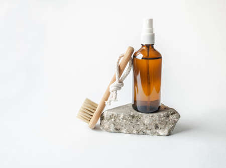 White bath background front view with glass brown cosmetic bottle on gray stone podium and woden brush. Isolated cosmetics concept. Stock fotó