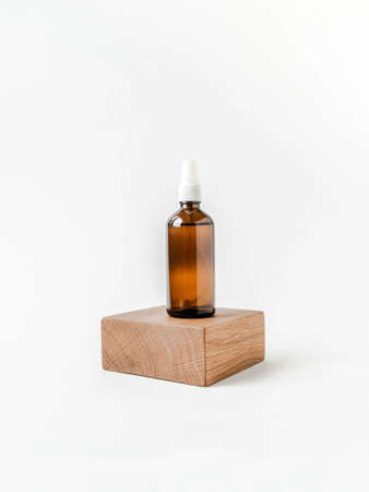 White background front view with glass brown cosmetic bottle on wood cube podium. Isolated cosmetics concept.