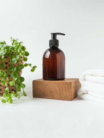 Brown bottle mockup for bathing products on wood podium, spa shampoo, shower gel, liquid soap and stacked white spa towels on white background. Front view. Copy space