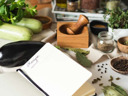Open notebook for cooking recipes and various vegetarian ingredients on kitchen table. Front view