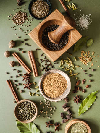 Various dry spices in small bowls and scattered on green background. Top view