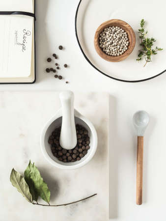 Kitchen background with various kitchen utensils, spices and recipe pad on light background. Top view