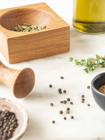 Herbs and spices cooking on marble table. Wood mortar and pastle and various spices and herbs. Front view. Copy space