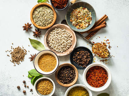 Various dry spices in small bowls and herbs flat lay on gray background. Top view. Copy space