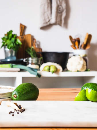 Wooden table with green fruit and marble board and blurred kitchen background. Copyspace. Concept of food preparation, kitchen on background.