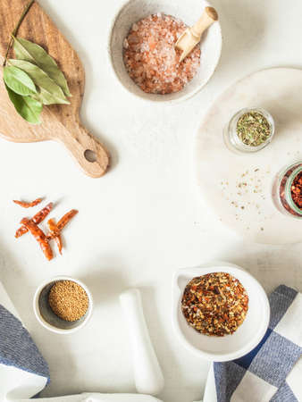 Various dry spices and dry vegetables in mortar and glass jars flat lay on kitchen table flat lay. Top view. Copy space