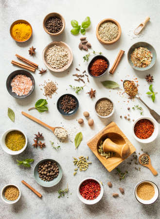 Various dry spices in small bowls and raw herbs flat lay on gray background. Top view Stock fotó