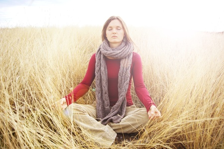Beautiful young woman meditating in a open field in the long autumn grass photo