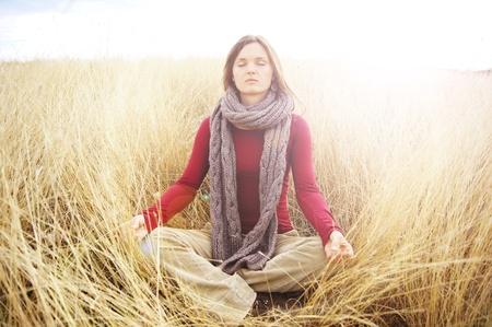 mujer meditando: Meditando joven y bella mujer en un campo abierto en el pasto largo oto�o