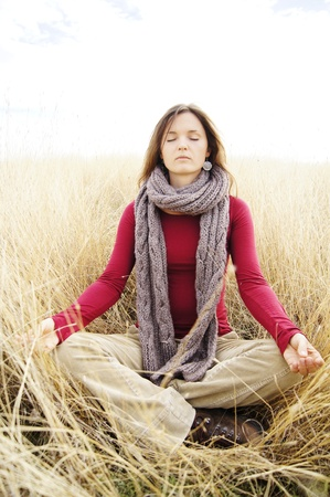 Beautiful young woman meditating in a open field in the long autumn grass Stock Photo - 10967903