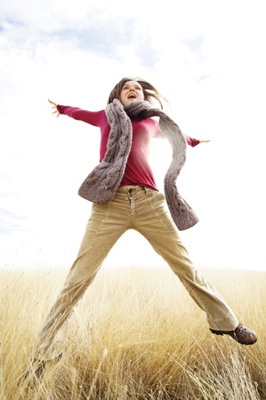 Beautiful young girl jumping with joy in a long grass field                       photo