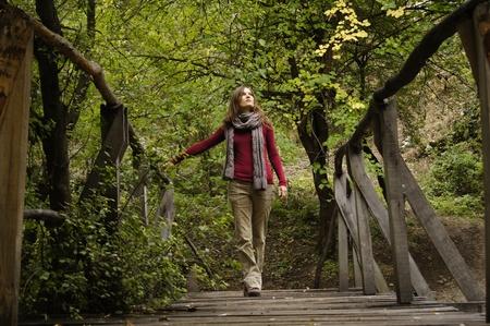 Beautiful young woman crossing a wooden bridge