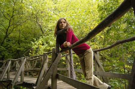 handrail: Beautiful young girl leaning on the handrail of a wooden bridge