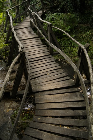 Winding wooden bridge over a river photo