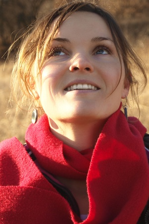 Happy young woman with a red scarf looking at the sky and smiling Stock Photo - 11134044