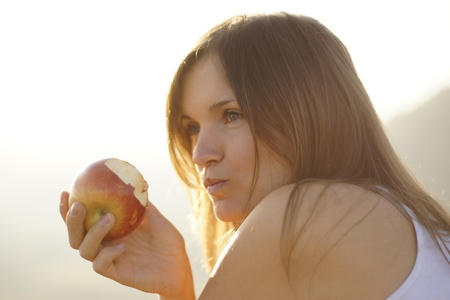 Beautiful young woman eating a red apple in bight sun photo