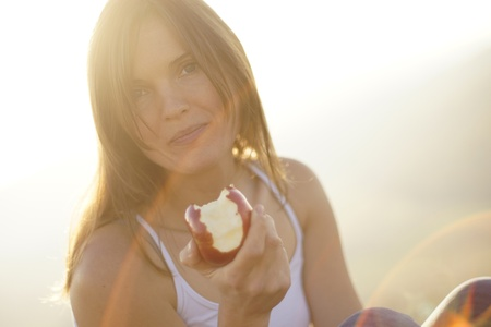 radiant light: Beautiful young woman eating a red apple in bight sun