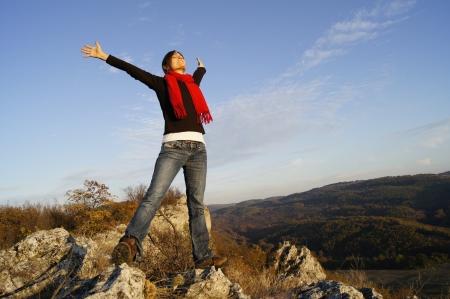 растягивание: Молодая девушка растяжение руки на вершине успеха чувство горных
