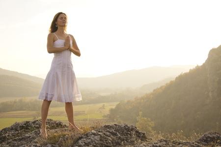 namaste: Joven mujer de pie en la meditaci�n sobre la cima de una colina