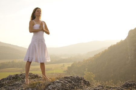 enlighten: Young woman standing in meditation on the top of a hill