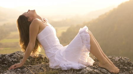 Beautiful young girl with a white dress sitting on a rock