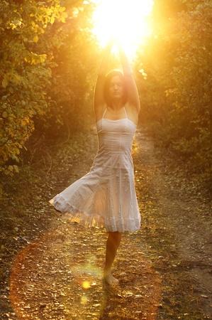 iluminados: Joven mujer meditando en equilibrio sobre una pierna en un camino de tierra Foto de archivo