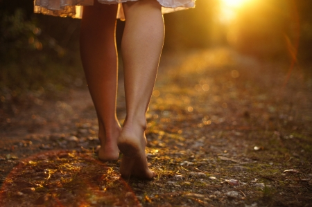 dirt road: Young female legs walking towards the sunset on a dirt road