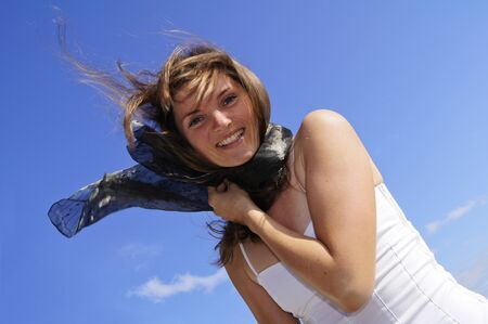 Beautiful young woman in white dress smiling against a blue sky background Stock Photo - 12465491