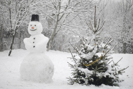 Snow falling over a snowman and a christmas tree  photo