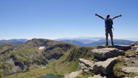 Excursionistas en las montañas de Rila Mujer, Bulgaria, con los brazos abiertos a disfrutar de los paisajes de montaña