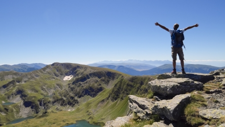 Male hiker in Rila mountains, Bulgaria, with arms stretched out to enjoy the mountain scenery photo