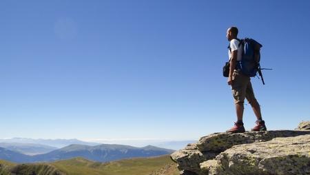 bergbeklimmen: Man wandelaar staande met rugzak op rots met uitzicht op bergketen Stockfoto
