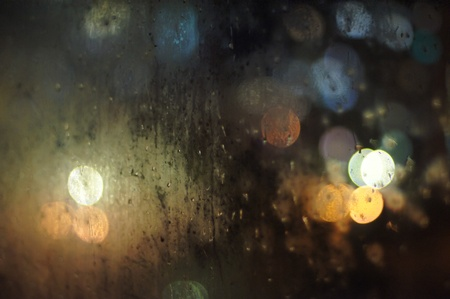 Raindrops on a window with out of focus street lights background photo