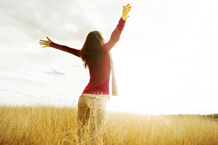 Young girl spreading hands with joy and inspiration facing the sun photo