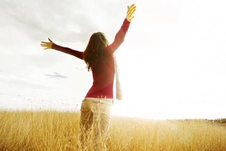 喜びとインスピレーション、太陽に直面して手を広がっている若い女の子