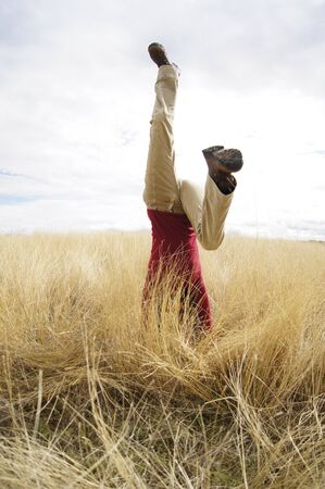 headstand: Young girl doing headstand in a filed of long grass