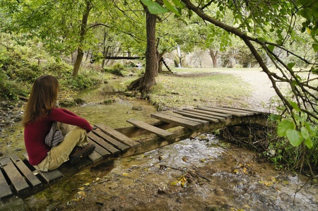 Beautiful young girl relaxing on a wooden bridge in the forest photo
