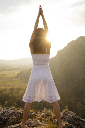 yoga sunset: Young woman standing on a rock greeting the light of the sun Stock Photo