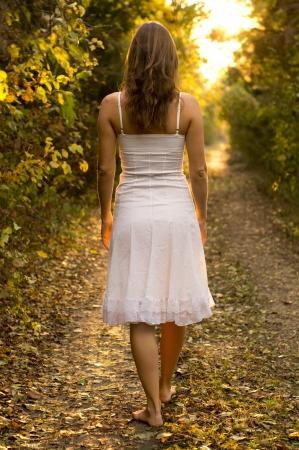 piedi nudi di bambine: Giovane ragazza con il vestito bianco, cammina su un sentiero nella foresta misteriosa