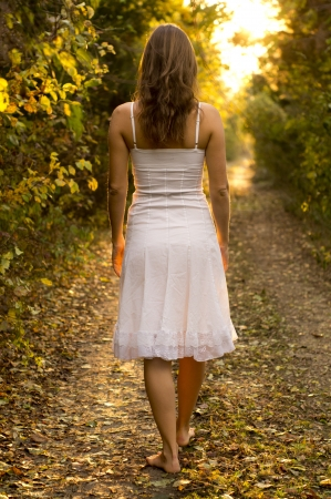 Young girl with white dress walking onto a mysterious path in the forest photo