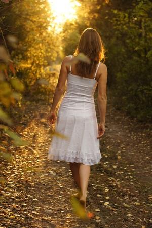 Junges Mädchen mit weißem Kleid zu Fuß auf einem geheimnisvollen Weg in den Wald